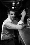 человек в белой рубашке сидя около бара Стоковая Фотография