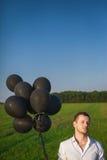 Человек в белой рубашке с черными воздушными шарами в поле Стоковое Изображение