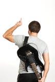 Человек в вскользь носке, держащ гитару и положение изолированный дальше стоковое фото rf