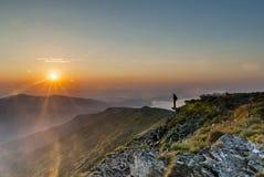 Человек в горах на восходе солнца Стоковые Фотографии RF