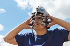 Человек в голубой рубашке носит средневековый шлем с кожаными ремнями Стоковое Фото