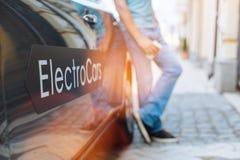Человек в голубых джинсах полагаясь на его новом электрическом автомобиле Стоковые Изображения RF
