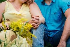 Человек в голубых одеждах и женщина в желтом платье сидят стоковые фото