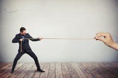 Человек в деловом костюме вытягивает веревочку Стоковые Изображения RF