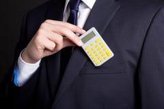 Человек в деловом костюме кладя калькулятор в карманн Стоковое Фото