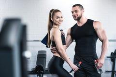 Человек в женщине держа бутылки воды и обнимая в спортзале Стоковое фото RF