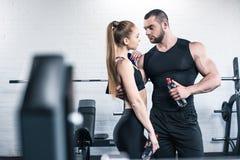 Человек в женщине держа бутылки воды и обнимая в спортзале Стоковая Фотография RF