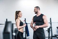Человек в женщине держа бутылки воды и смотря один другого Стоковое Изображение