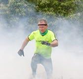 Человек в желтых одеждах скача над огнем и дымом Стоковое Изображение RF