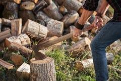 Человек в джинсах и рубашке стоя около пня с осью в руках Стоковая Фотография