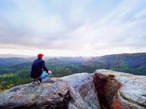 Человек в джинсах чернит внешнюю фуфайку и красное пребывание крышки в конце треснутой скалистой скалы Стоковые Фото
