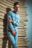 Человек в джинсовой ткани представляя в студии пока касающся его руке Стоковая Фотография RF