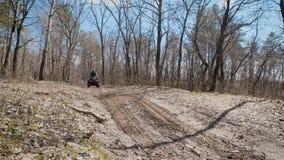 Человек в защитной одежде и шлеме быстро едет велосипед квада вдоль леса вдоль песочной дороги, там акции видеоматериалы