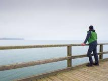 Человек в зеленом цвете на моли моря на поручне Туман осени, дождливый день Стоковое Изображение