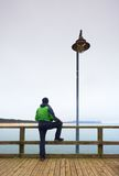 Человек в зеленом цвете на моли моря на поручне Туман осени, дождливый день Стоковые Фотографии RF