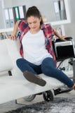 Человек в инвалидной коляске пробуя сидеть на софе сама Стоковое Изображение RF