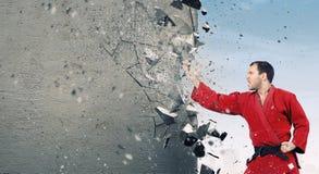 Человек в кимоно ломая стену Стоковые Фото