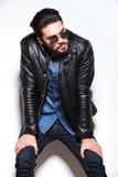 Человек в кожаной куртке и sunlasses смотря к его стороне Стоковое Изображение