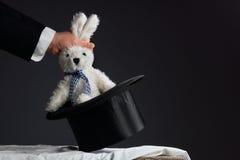 Человек в костюме вытягивая кролика из шляпы Стоковые Фото