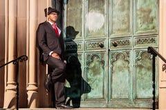 Человек в костюме держа склонность на здании Стоковое фото RF