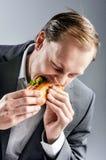 Человек в костюме ест BLT полно страстного желания Стоковые Фотографии RF
