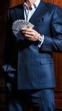 Человек в костюме представляет с карточками на деревянной предпосылке Стоковая Фотография RF