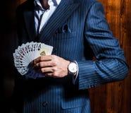 Человек в костюме представляет с карточками на деревянной предпосылке Стоковое фото RF