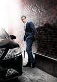 Человек в костюме представляя около автомобиля Стоковые Фотографии RF
