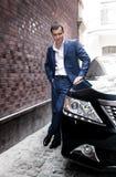 Человек в костюме представляя около автомобиля Стоковые Фото