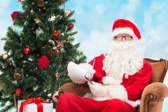 Человек в костюме Санта Клауса с блокнотом Стоковые Фотографии RF
