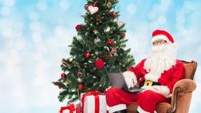 Человек в костюме Санта Клауса с компьтер-книжкой Стоковое Фото