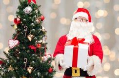 Человек в костюме Санта Клауса с подарочной коробкой Стоковое Изображение