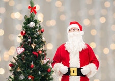 Человек в костюме Санта Клауса с рождественской елкой Стоковые Изображения