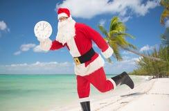Человек в костюме Санта Клауса с часами Стоковая Фотография