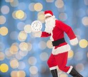 Человек в костюме Санта Клауса с часами Стоковое Изображение