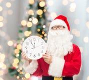 Человек в костюме Санта Клауса с часами Стоковые Фото