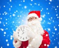 Человек в костюме Санта Клауса с часами Стоковые Фотографии RF