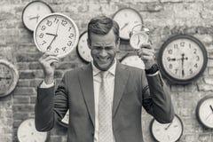 Человек в костюме стоя близко стена с часами Стоковые Фотографии RF
