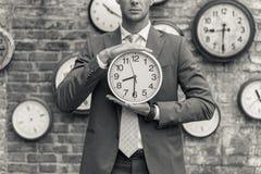 Человек в костюме стоя близко стена с часами Стоковое Фото