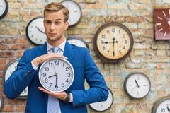 Человек в костюме стоя близко стена с часами Стоковые Фото
