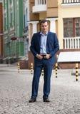 Человек в костюме стоя на дороге Стоковые Изображения