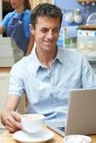 Человек в кофейне используя портативный компьютер Стоковые Фото