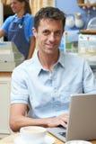 Человек в кофейне используя портативный компьютер Стоковые Фотографии RF