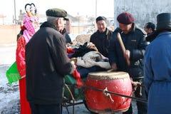 Человек в красном традиционном пальто ударил барабанчик Стоковое фото RF