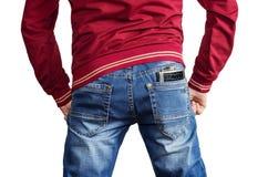 Человек в красном шлямбуре и голубые джинсы с склянкой металла в его подпирают карманн стоковые изображения