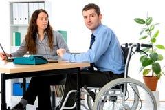 Человек в кресло-коляске и его женский коллега работая в jo стоковое изображение rf