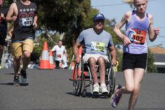 Человек в кресло-коляске наслаждаясь бегом потехи стоковые фото