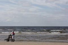 Человек в кресло-коляске на пляже Стоковые Фото
