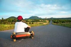 Человек в крышке и с длинной доской в его руках сидит на проселочной дороге стоковое изображение