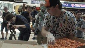 Человек в крышке положил красочные донуты на таблицу в торговый центр справедливо люди сток-видео